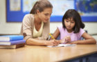 Shot of a teacher working with a young students while sitting in a classroom