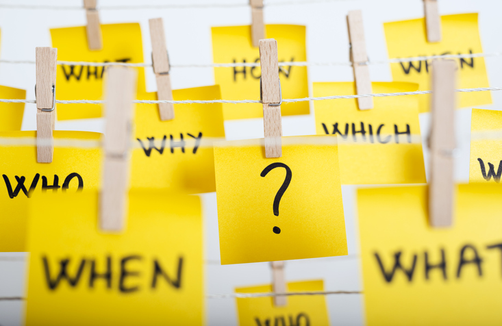 adhesive note papers with question mark and w questions hanging on the rope